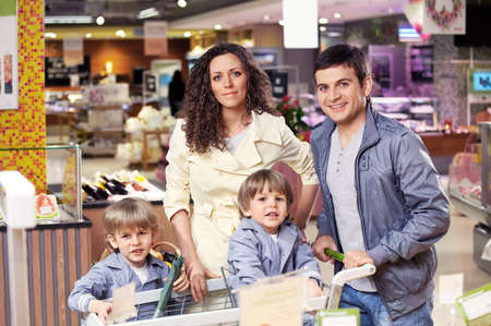 Parents and their children in grocery shop photo