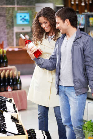 The young couple chooses wine in shop photo