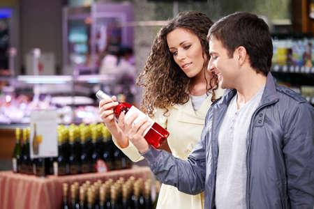 buying: The young couple chooses a wine bottle in shop Stock Photo
