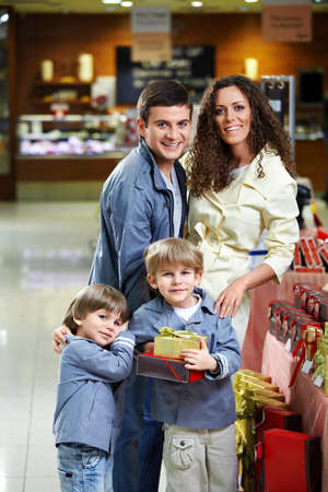 Happy family in shop with boxes of gifts photo