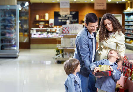 Happy family with boxes of gifts in shop in the foreground