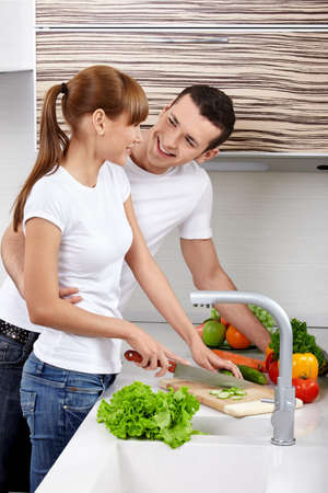 vegetables young couple: The young girl with the young man cuts vegetables on kitchen Stock Photo