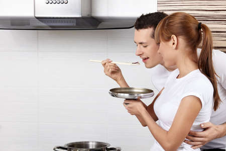 The young girl spoon-feeds the man on kitchen  photo