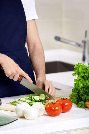 The man in an apron cuts cucumbers close up photo