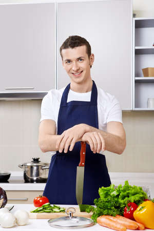 aprons: The young man in an apron with a knife at kitchen Stock Photo