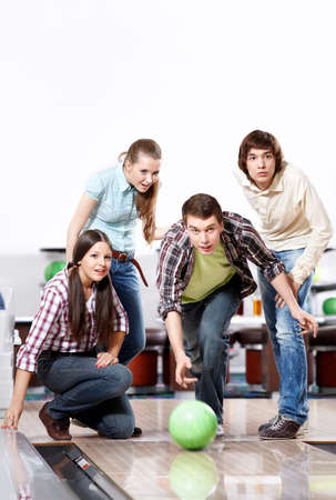 recreational pursuit: The youth observes as the young man throws a sphere for bowling Stock Photo