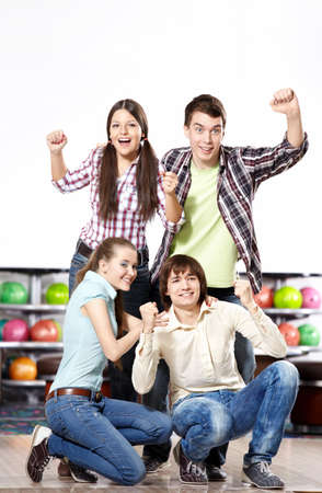 Young attractive people rejoice at game in bowling photo