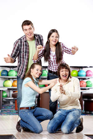 rejoice: Four young friends rejoice to a successful throw in bowling