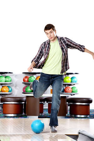 The young man kicks a sphere for bowling photo