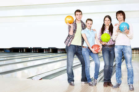 Young men and girls stand with spheres for bowling
