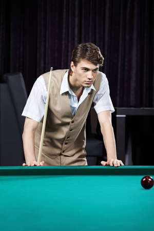 The young attractive man plays billiards photo