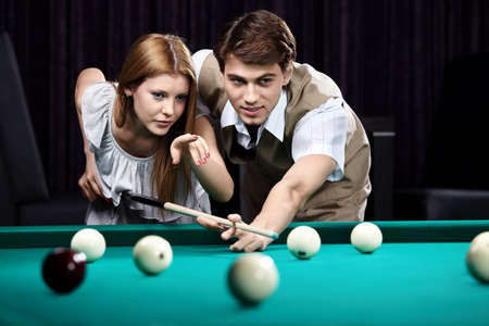 pool balls: The young girl and the guy discuss a blow trajectory Stock Photo