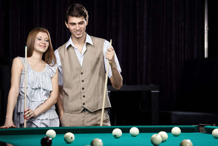 The young attractive couple plays billiards   photo