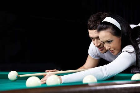 Les objectifs de la jeune couple dans le jeu de billard par fermer