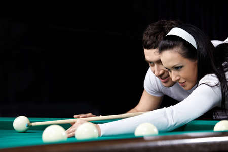 billiards tables: The young couple aims in game billiards by close up