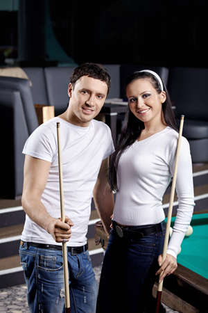 Young couple with cue at a billiard table photo