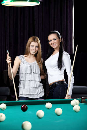 Two young attractive girls play billiards photo