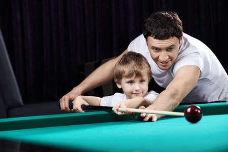 Le père de la jeune apprend le fils de jouer de billard Banque d'images
