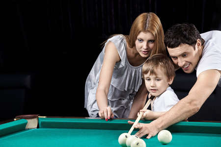 prompt: Young parents prompt to the boy how to play billiards Stock Photo