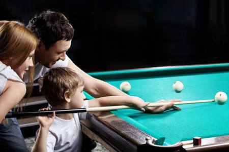 The young couple and the child plays billiards photo