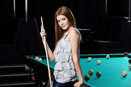 billiards tables: The nice young girl with cue at a billiard table