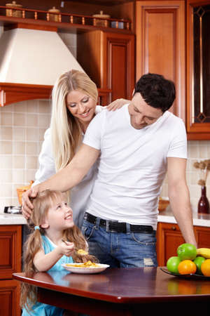 Parents look at the child which eats corn-flakes on kitchen photo