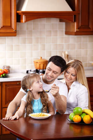 The father feeds the daughter from a spoon with a breakfast photo