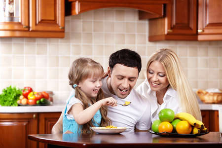 The young family has breakfast with the child on kitchen photo