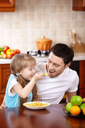 The little girl spoon-feeds the daddy on kitchen photo