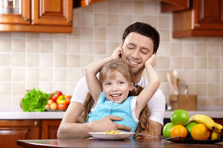 The daughter embraces the daddy on kitchen photo