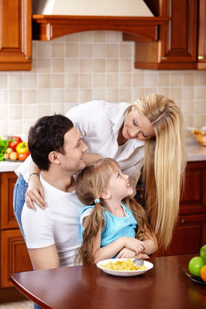 Happy family with the child in kitchen during a breakfast photo
