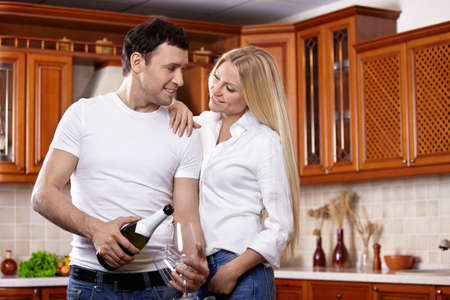 The young man pours champagne in glasses with the girl on kitchen photo
