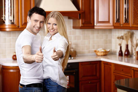 The young couple shows thumbs upwards on kitchen photo