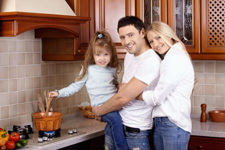 Parents with the child prepare at cooker photo