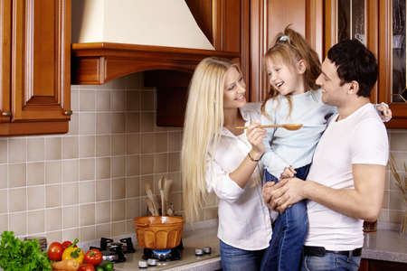 domestic kitchen: The happy young family prepares in kitchen Stock Photo
