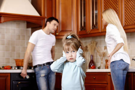 people arguing: The girl in the foreground at quarrel of parents