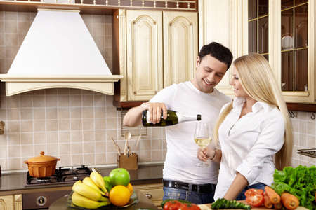 The young man pours champagne to the girl on kitchen photo