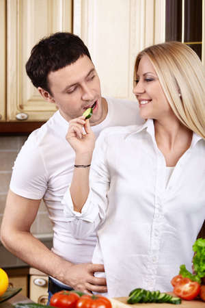 The attractive girl treats the young man on kitchen Stock Photo - 7861584