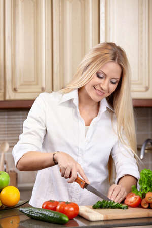 The attractive woman cuts vegetables on kitchen photo