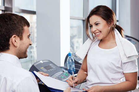 The attractive girl appends the signature in fitness club photo