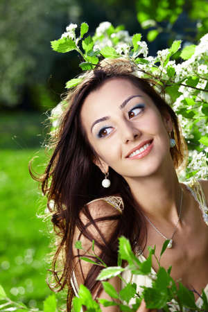 The beautiful young girl in blossoming trees