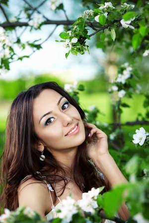 The nice girl against a green tree with colours Stock Photo - 7931950
