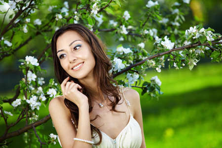 The beautiful young girl against a blossoming tree photo