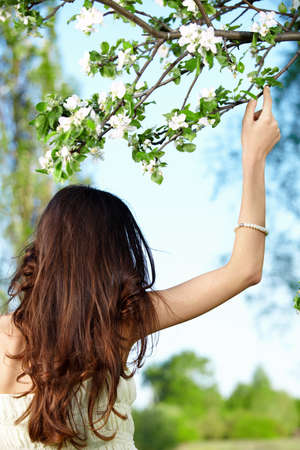 The girl holds a hand a tree branch photo