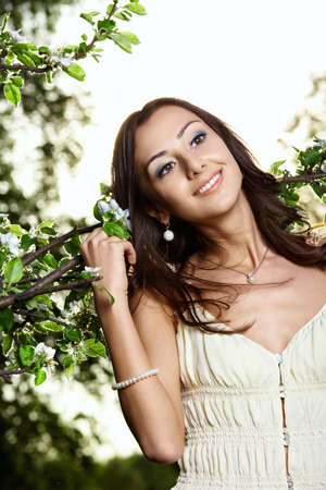 Portrait of the nice young girl in blossoming trees photo