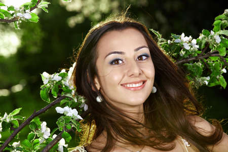 The smiling nice girl in greens of trees photo