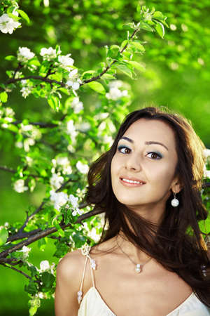 The attractive young girl in greens of trees photo