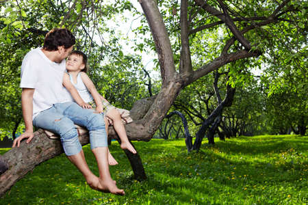 The daddy and the son sit on a tree in forest Stock Photo - 7931987