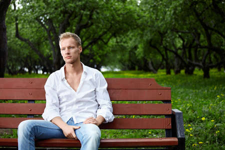 The young guy sits on a bench in park photo