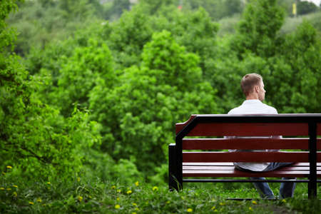 The young man sits one on a bench against green trees photo